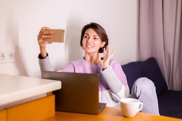 ソファの上の寝室で若い白人の女の子の女性は携帯電話のカメラを見てください