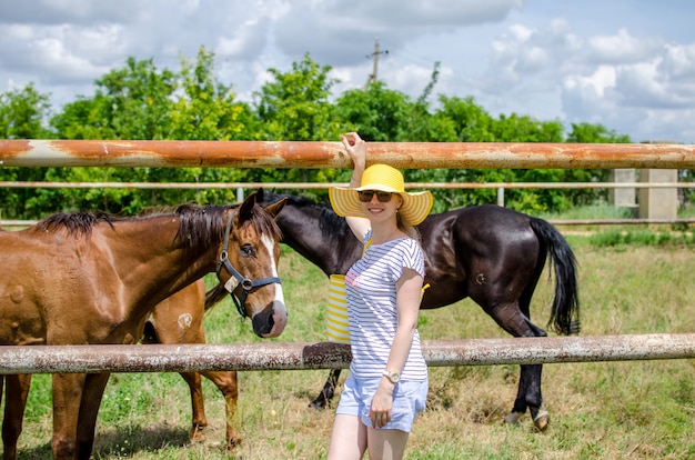 Young caucasian girl in a yellow hat and summer clothes standing near the paddock with horses, smiling and looking at the camera. excursion to the stud farm with animals. copy spase