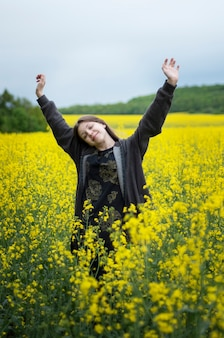 Young caucasian  girl on yellow rapeseed field Premium Photo