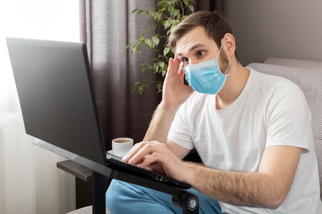 Young caucasian gloomy man in stress working from home office wearing protective mask using laptop and internet. coronavirus covid 19 quarantine. remote work, freelancer, home office workplace on sofa