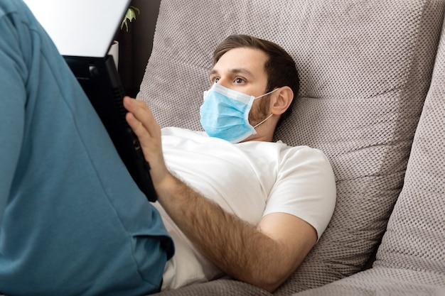 Young caucasian gloomy man working from home office wearing protective mask using laptop and internet. coronavirus covid 19 quarantine. remote work, freelancer, home office workplace on sofa