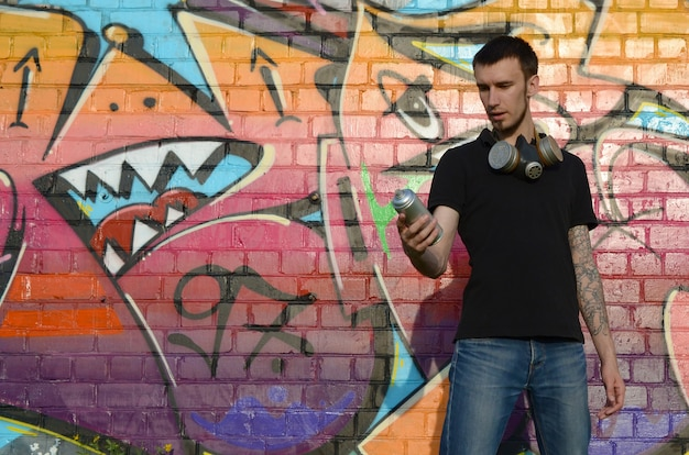 Young caucasian graffiti artist in black t-shirt with silver aerosol spray can near colorful graffiti in pink tones on brick wall. street art and contemporary painting process