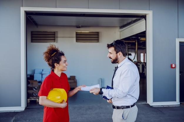 若い白人のグラフィックエンジニアが彼の女性従業員にタスクで紙を与えます。彼らはプリントショップの前に立っています。