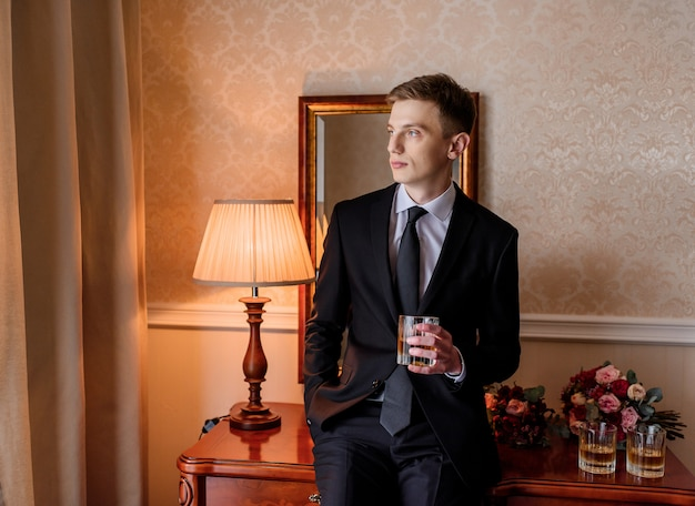 Young caucasian groom dressed in stylish tuxedo drinking alcohol in room and sitting on the table next to bridal bouquets