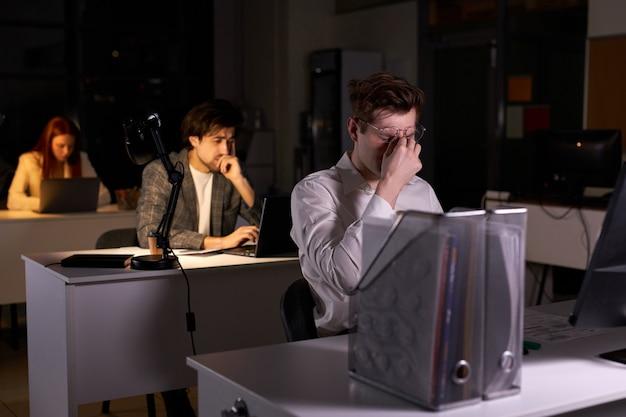 우울증과 만성 업무 피로가 있는 정장 차림의 젊은 백인 남자, 더 많은 수면과 휴식이 필요합니다. pc 컴퓨터를 사용하여 책상에 앉아 지친 남자, 직장에서 작업에 대해 생각하는 데 지쳤습니다.