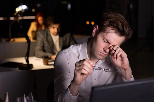 밤에 사무실에서 정장을 입은 젊은 백인 남자, 과로로 눈이 아프고 더 많은 수면과 휴식이 필요합니다. pc 컴퓨터를 사용하여 책상에 앉아 지친 남자, 직장에서 작업에 대해 생각하는 데 지쳤습니다.