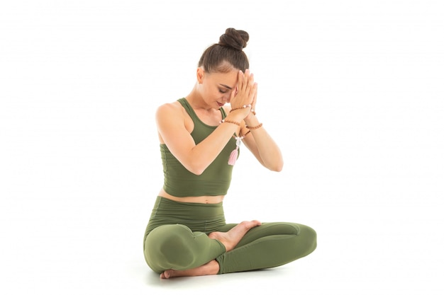 Young caucasian gymnast with athletic body sits on a floor in lotus position, doing yoga and meditating