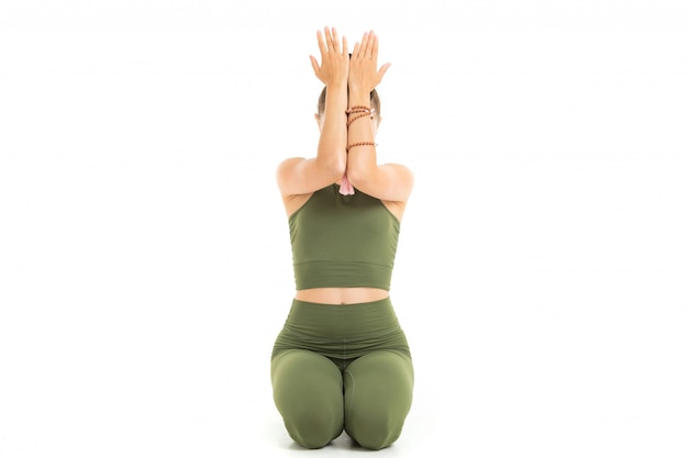 Young caucasian gymnast with athletic body sits on a floor with closed eyes, doing yoga and meditating isolated on white background