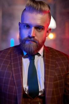 暗い煙のような部屋のソファに座っているスーツを着た若い白人ハンサムなひげを生やした男