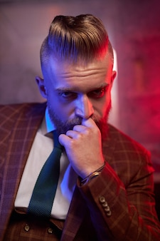 Young caucasian handsome bearded man in suit sitting on couch in a dark smoky room