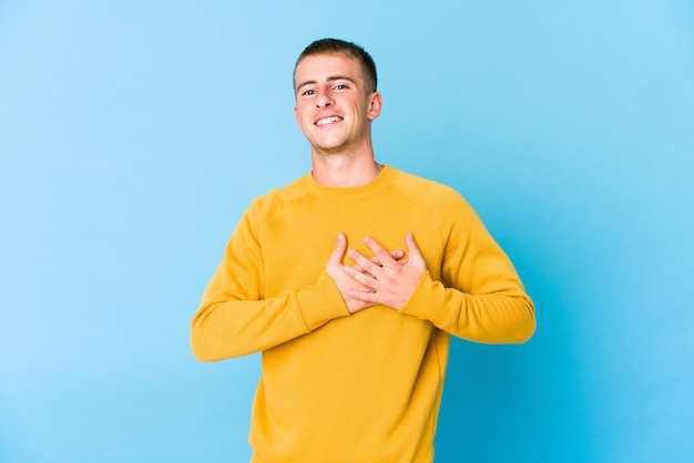 Young caucasian handsome man has friendly expression, pressing palm to chest. love concept.