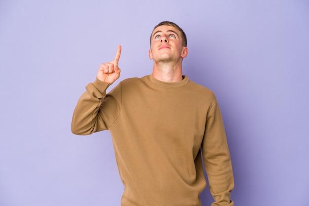 若い白人のハンサムな男は、両方の前指で空白を示していることを示しています。