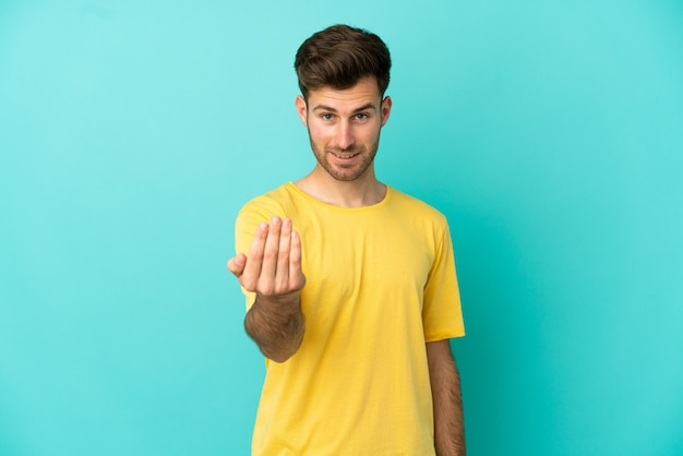 Young caucasian handsome man isolated on blue background inviting to come with hand. happy that you came