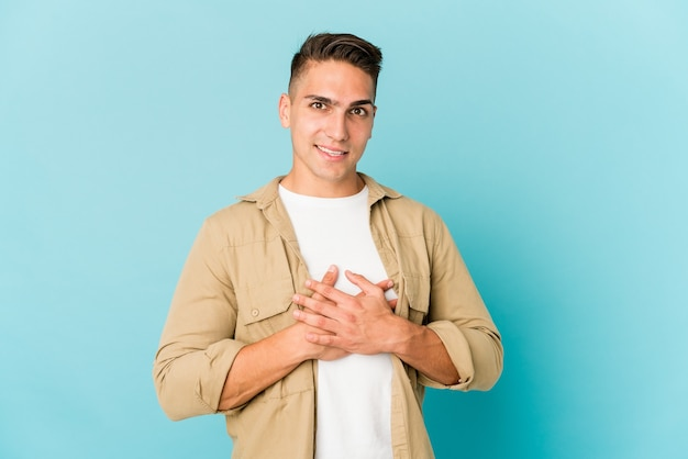 Young caucasian handsome man isolated has friendly expression, pressing palm to chest. love concept.