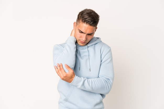 Young caucasian handsome man isolated massaging elbow, suffering after a bad movement.