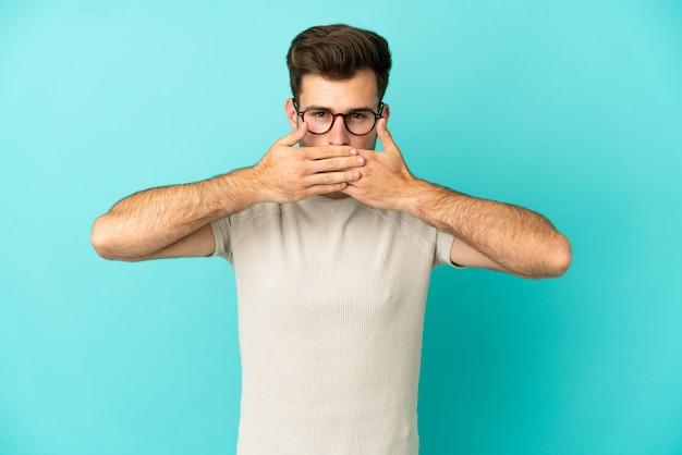 手で口を覆う青い背景に分離された若い白人ハンサムな男