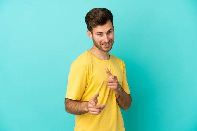 正面を指して笑っている青い背景に分離された若い白人ハンサムな男