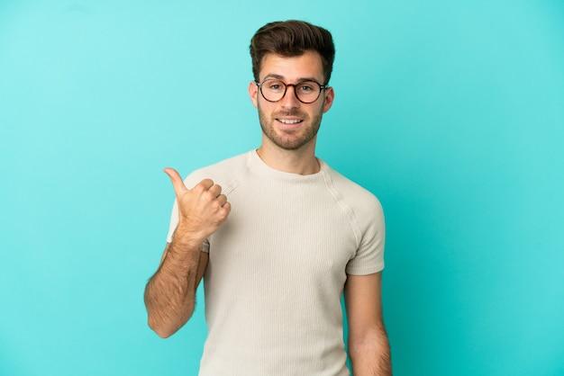 製品を提示する側を指している青い背景に分離された若い白人ハンサムな男