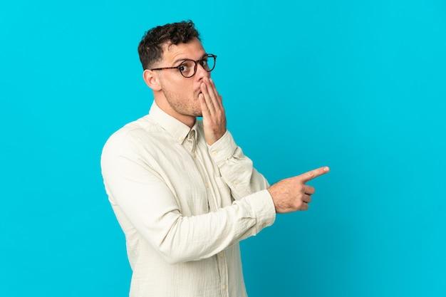측면을 가리키는 동안 놀라운 표정으로 파란색 배경에 고립 된 젊은 백인 잘 생긴 남자