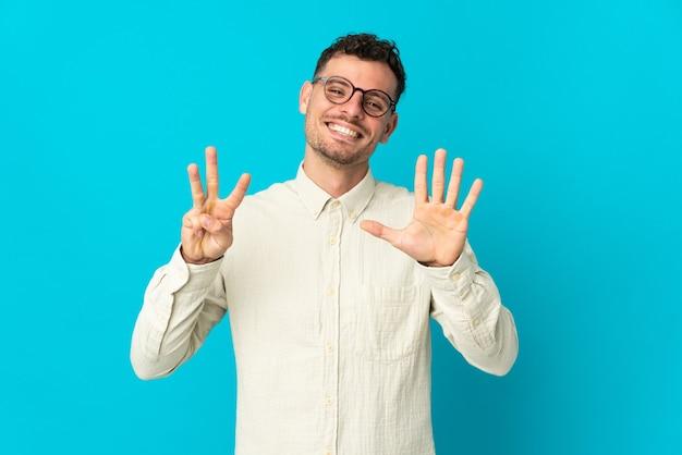 손가락으로 8 세 파란색 벽에 고립 된 젊은 백인 잘 생긴 남자