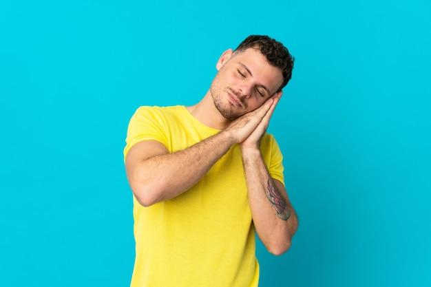 愛らしい表情で睡眠ジェスチャーを作る青い壁に分離された若い白人ハンサムな男