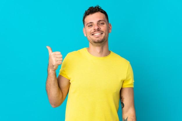 製品を提示する側を指している青い壁に分離された若い白人ハンサムな男