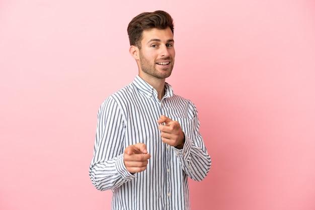 正面を指して笑顔のピンクの背景に分離された若い白人ハンサムな男