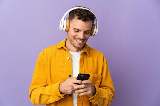 Молодой кавказский красавец изолирован на фиолетовой стене, слушает музыку и смотрит на мобильный