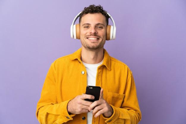 Молодой кавказский красавец изолирован на фиолетовой стене, слушая музыку с мобильного и смотрящую вперед