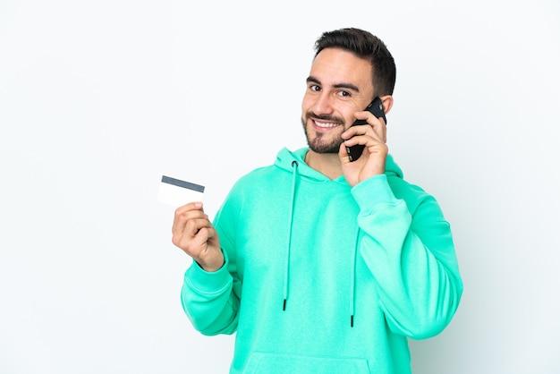 Молодой кавказский красавец, изолированные на белом фоне, разговаривает по мобильному телефону и держит кредитную карту