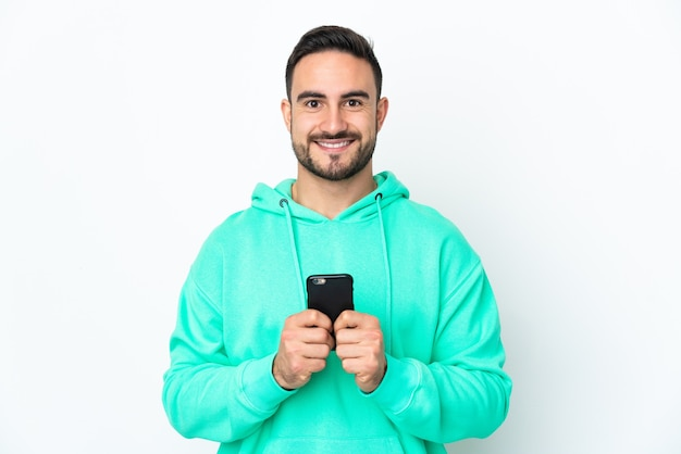 カメラを見て、携帯電話を使用しながら笑っている白い背景で隔離の若い白人ハンサムな男