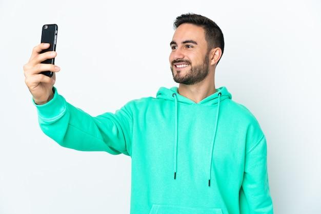 携帯電話でselfieを作る白い背景で隔離の若い白人ハンサムな男