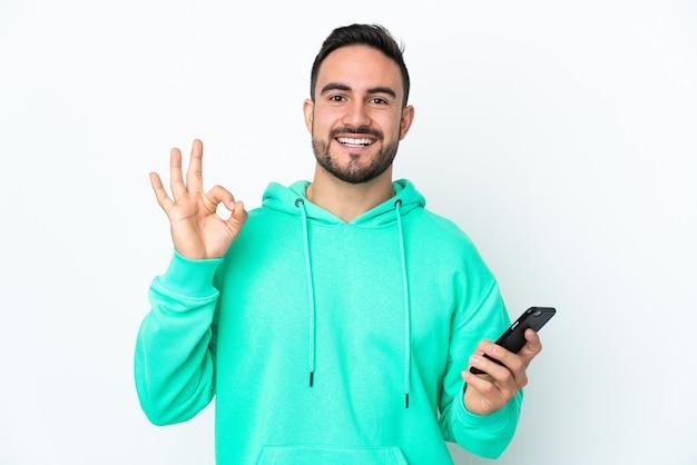 Молодой кавказский красавец изолирован на белом фоне с помощью мобильного телефона и делает знак ок