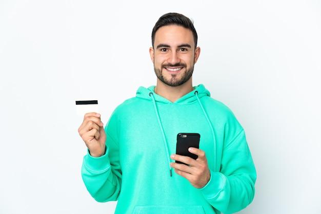 Молодой кавказский красавец изолирован на белой стене, покупая с мобильного телефона с помощью кредитной карты
