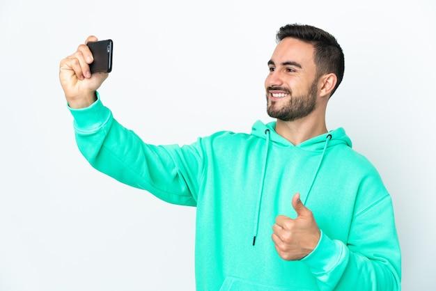 Молодой кавказский красавец изолирован на белой стене, делая селфи с мобильным телефоном