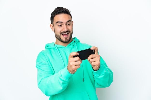 Молодой кавказский красавец изолирован на белой стене, играя с мобильным телефоном