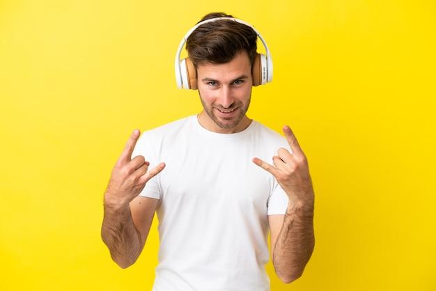 Молодой кавказский красавец изолирован на желтом фоне, слушая музыку, делая рок-жест