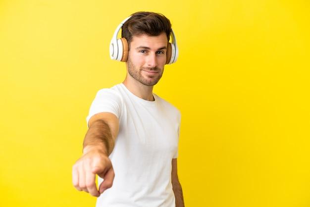 Молодой кавказский красавец изолирован на желтом фоне, слушая музыку