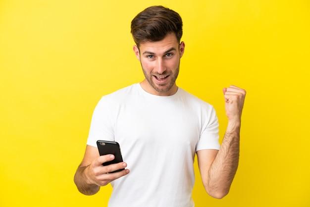 Молодой кавказский красавец изолирован на желтом фоне с помощью мобильного телефона и делает жест победы