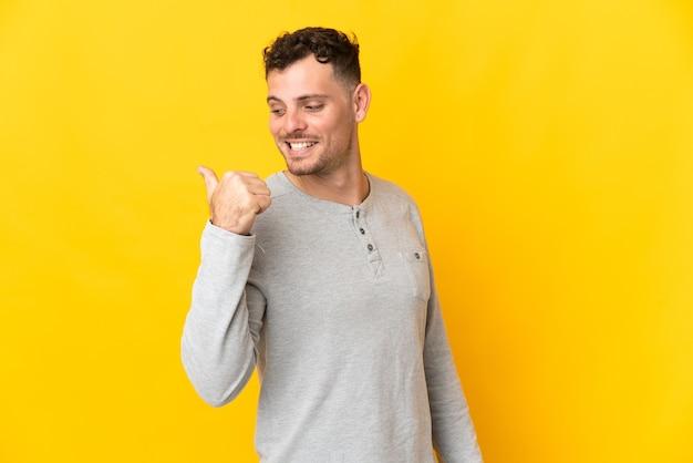 製品を提示する側を指している黄色の壁に分離された若い白人ハンサムな男