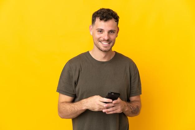 Молодой кавказский красавец изолирован на желтой стене, отправляя сообщение с мобильного телефона