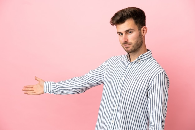 Young caucasian handsome man isolated on pink background extending hands to the side for inviting to come
