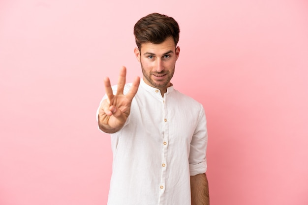 Young caucasian handsome man isolated on pink background happy and counting three with fingers