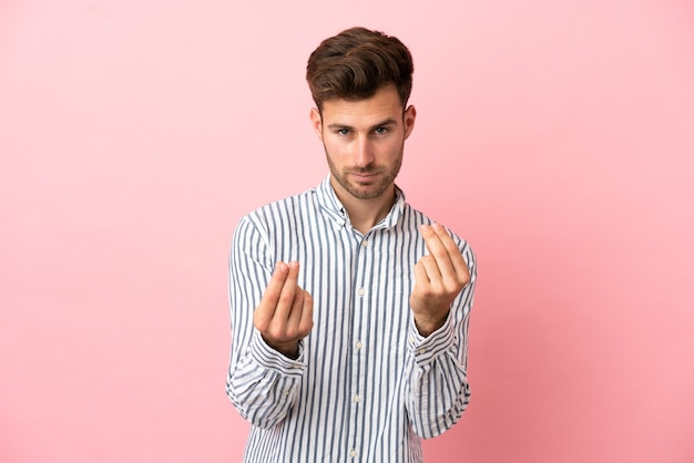 Young caucasian handsome man isolated on pink background making money gesture but is ruined