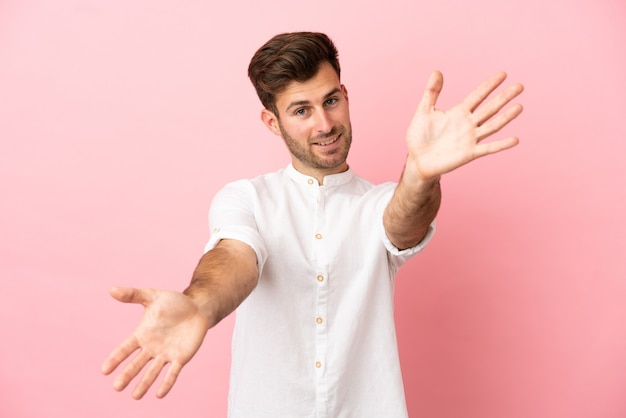 Young caucasian handsome man isolated on pink background presenting and inviting to come with hand