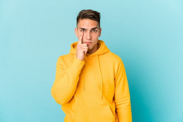 Young caucasian handsome man isolated showing number one with finger.