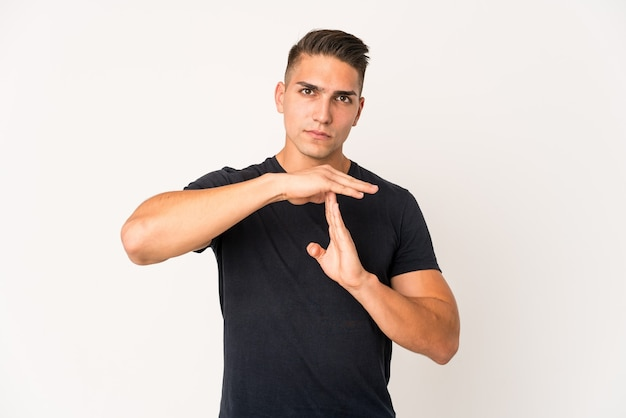 Young caucasian handsome man isolated showing a timeout gesture.