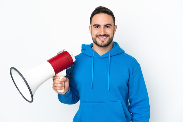 Young caucasian handsome man isolated on white background holding a megaphone and smiling a lot