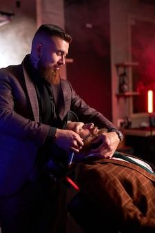 Молодой кавказский красавец на стуле парикмахера, имеющего процедуру бритья
