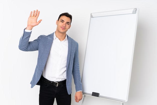 Young caucasian handsome man on purple wall giving a presentation on white board and saluting with hand